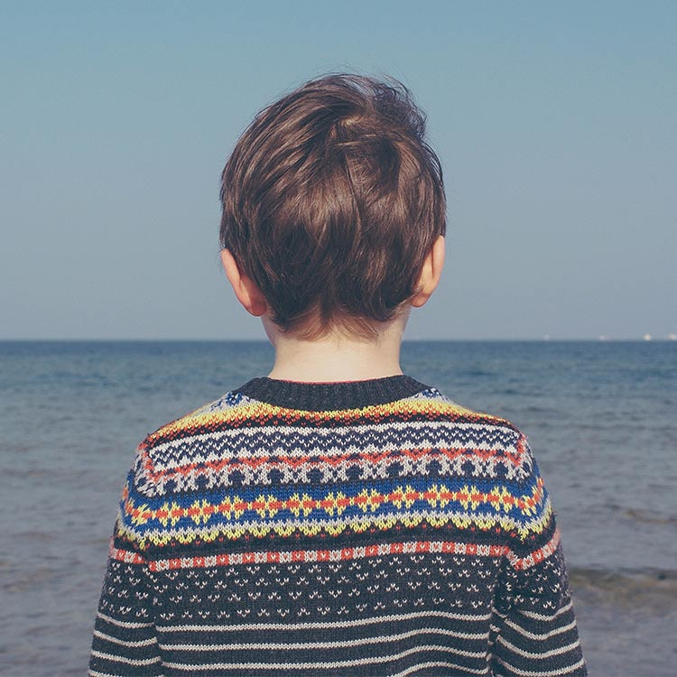 Boy_wearing_jumper_looking_out_to_sea