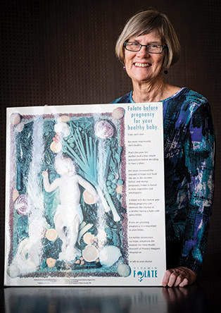 Professor Carol Bower with an early promotional poster for folate
